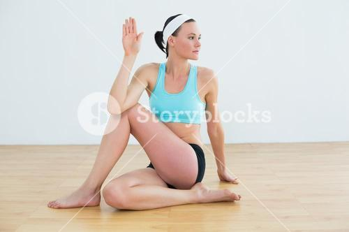 Woman doing the spine twisting pose at fitness studio
