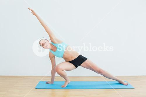 Slim woman doing the side plank yoga pose in fitness studio