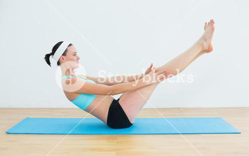 Fit woman doing the boat pose on yoga mat