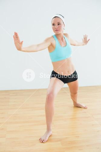 Toned woman doing the warrior yoga pose in fitness studio