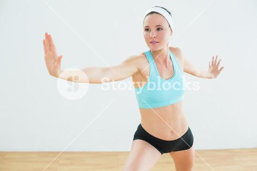 Woman doing the warrior yoga pose in fitness studio