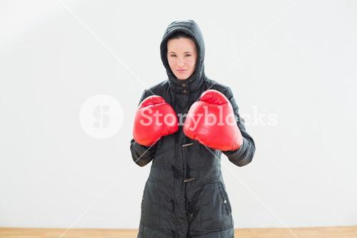 Tough woman in hooded jacket and red boxing gloves