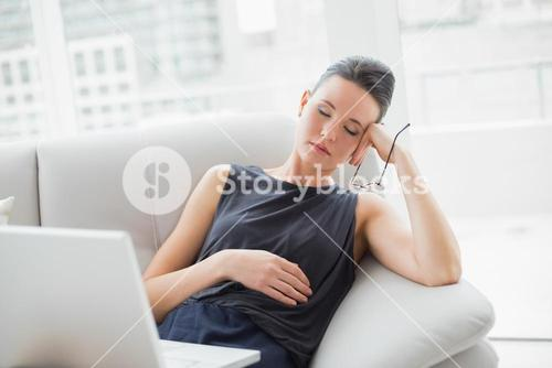 Beautiful well dressed woman resting on sofa while using laptop