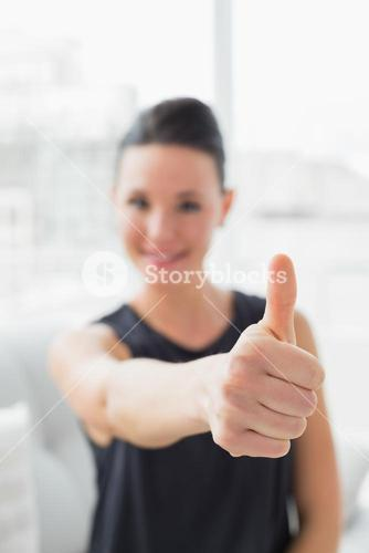 Blurred smiling well dressed woman gesturing thumbs up