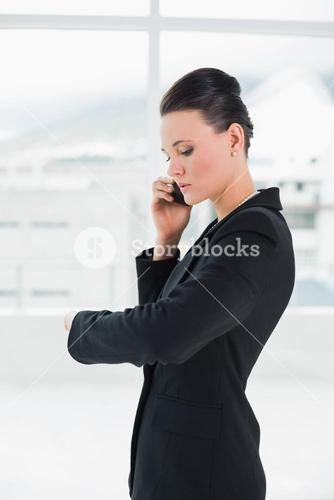 Elegant businesswoman using cellphone while checking time