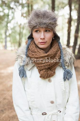 Woman wearing fur hat with woolen scarf and jacket in woods