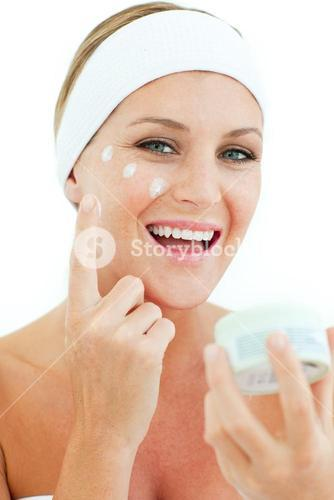 Woman putting cosmetic cream