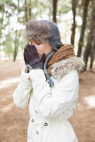 Woman in winter wear sneezing in woods