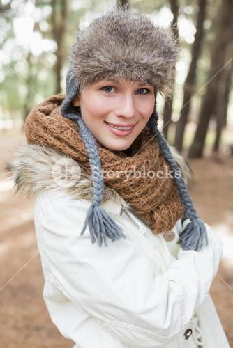 Woman in fur hat with woolen scarf and jacket in the woods