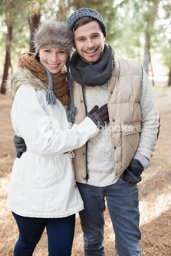Cheerful couple in winter clothing in the woods