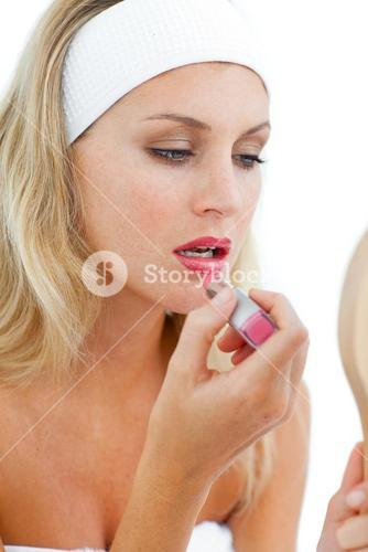 Concentrated woman applying lipstick