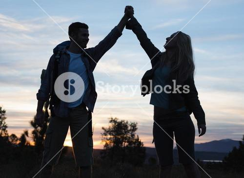 Silhouette couple holding up hands at dusk