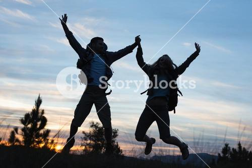 Silhouette couple jumping against the sky