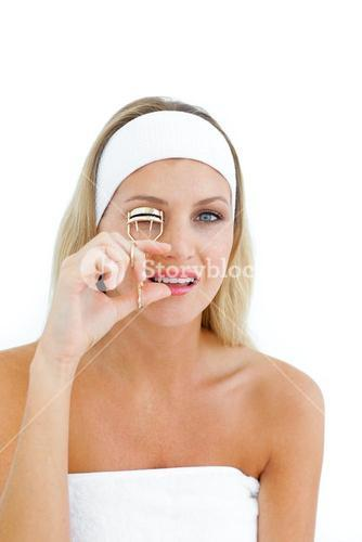 Attractive woman using an eyelash curler