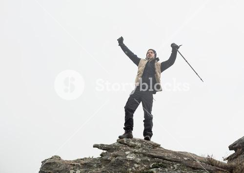Man with hands raised on rock against the sky