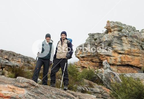 Couple standing on rocky landscape with trekking poles against clear sky