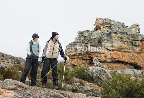 Couple on rocky landscape with trekking poles against sky