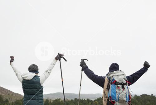 Rear view of couple raising hands after a trek
