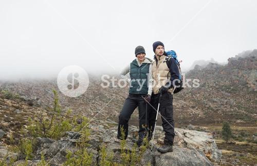 Couple standing on rock after a trek against clear sky