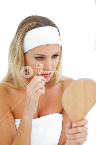 Charming woman using an eyelash curler