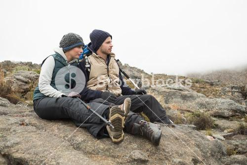 Couple sitting on rock with backpack and trekking poles