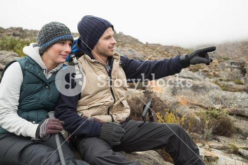 Couple on rock with trekking poles while on a hike