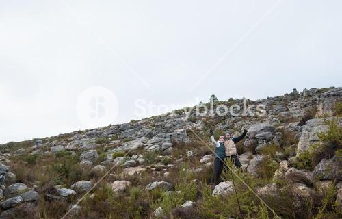 Couple standing on rocky landscape with hands raised against clear sky