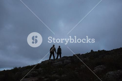Couple on rocky landscape against the sky at night