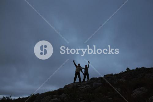 Couple raising hands on rocky landscape against sky at night