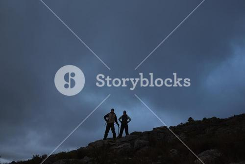 Couple with hands on hips on rocky landscape against sky at night