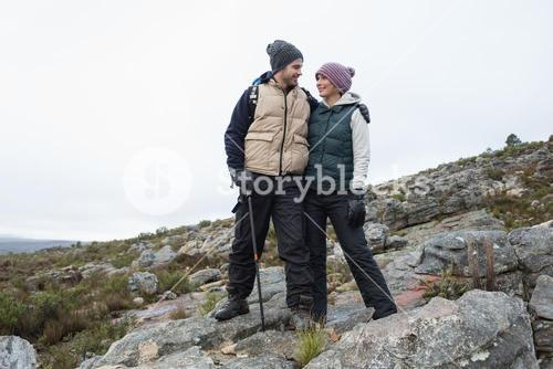 Couple standing on rocky landscape against the sky