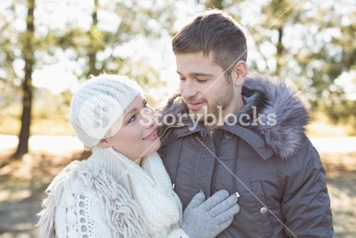 Smiling couple in winter clothing in the woods