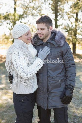 Loving couple in winter clothing in the woods