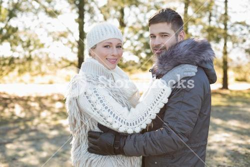 Loving young couple in winter clothing in the woods