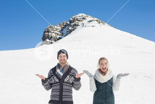 Couple with hands open standing in front of snowed hill