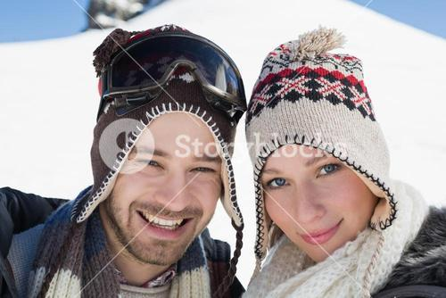 Smiling couple in woolen hats on snow covered landscape