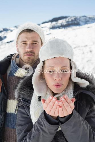 Couple with cupped hands on snow covered landscape