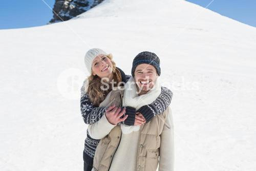 Couple in warm clothing on snowed landscape