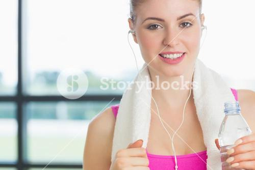 Woman holding water bottle in fitness studio