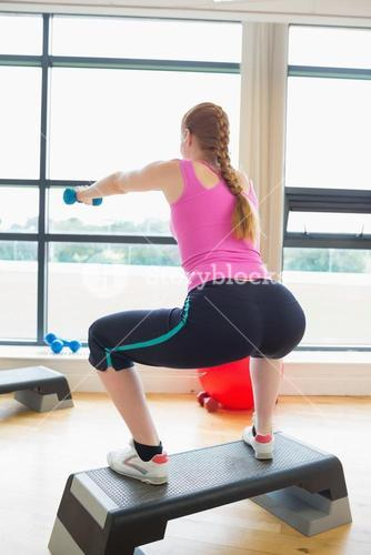 Woman performing step aerobics exercise with dumbbells