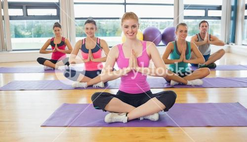 Class and instructor in Namaste position on exercise mats