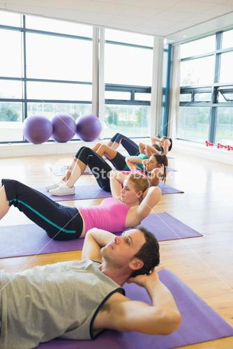 Sporty fitness class doing sit ups on exercise mats