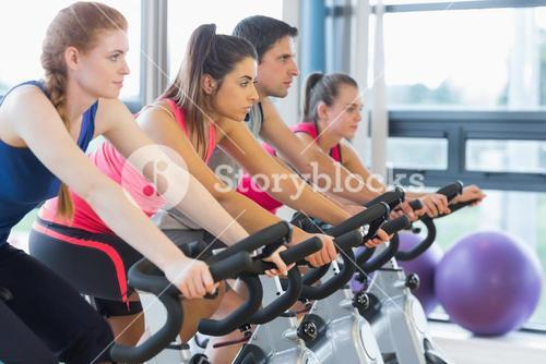 Four people working out at spinning class