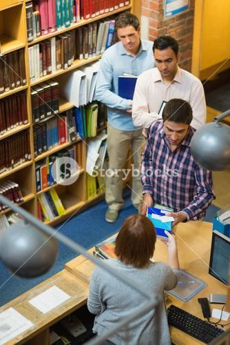 Mature students at counter in college library
