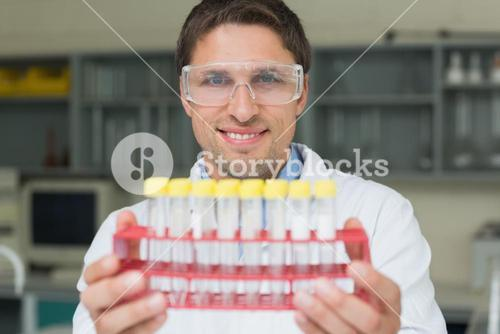 Smiling male researcher with test tubes in the lab