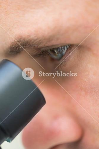 Extreme Close up of a scientific researcher using microscope