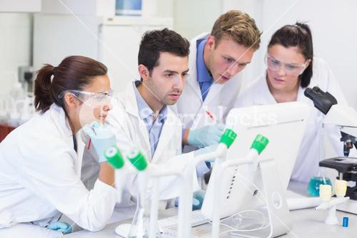 Researchers looking at computer screen in the lab