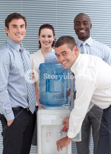 Busines people standing around water cooler in workplace