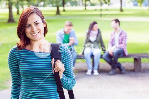 College girl smiling with blurred students in park