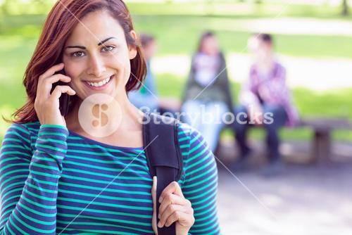 College girl using mobile phone with blurred students in park